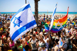 People waving two large Israel flags and one large Jewish LGBTQ pride flag on a beach in Israel