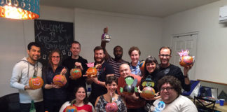 Attendees at a Tribe 12 LGBTQ event holding decorated pumpkins