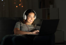 Teen girl watches YouTube videos with headphones on in a dark room