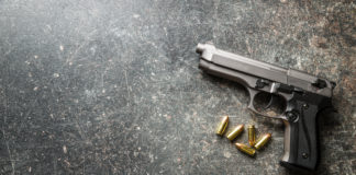 A gun on the ground with its bullets taken out beside it