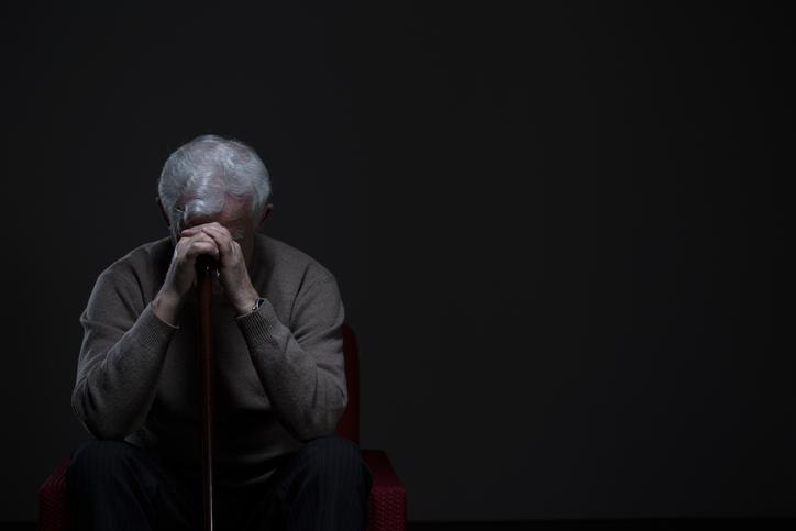 Elderly man sitting with head down on cane