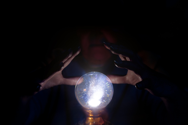 A soothsayer's hands hover over a crystal ball
