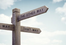 a sign pointing in different directions reading this way, that way, the other way