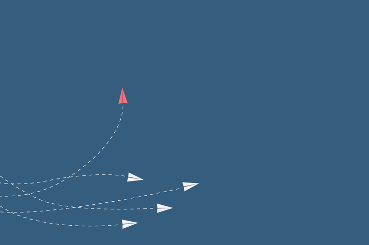 a group of white paper planes flies forward while one red paper plane swerves to the left