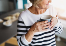 An aging woman holds a mug