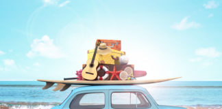 car driving along the beach with a pile of luggage on top