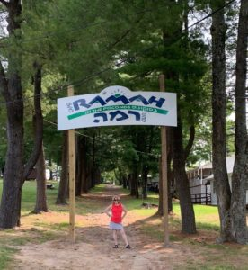 Harriet Levin stands under a sign reading Camp Ramah in the Poconos