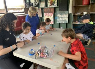 Harriet Levin helps children sitting at a table at Camp Ramah in the Poconos