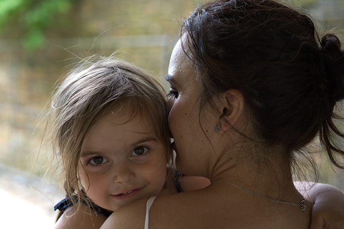 A woman holds a young child