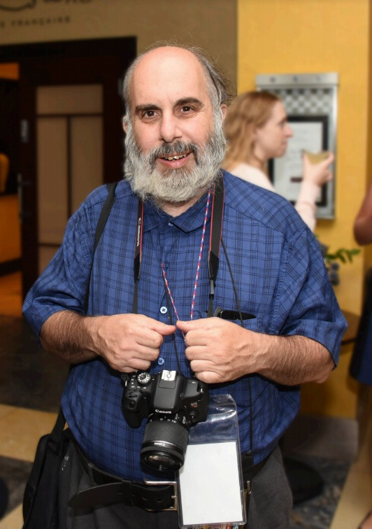 Robert Mendelsohn with a camera around his neck