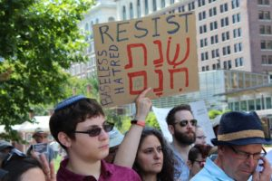 a group of protesters with one holding a sign that says resist, baseless hatred and some words in hebrew