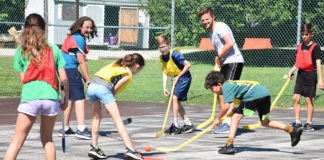 kids play with hockey sticks