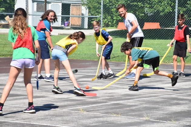 kids play with hockey sticks