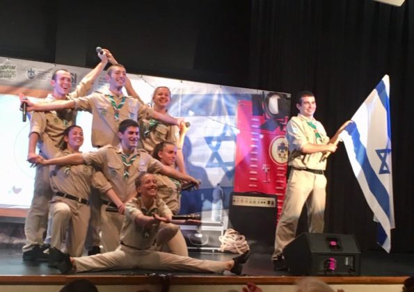 The Israel Scouts Friendship Caravan members make a Jewish star with their arms while another member holds an Israeli flag