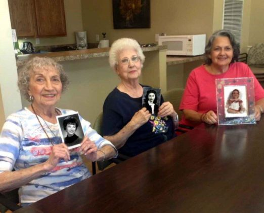 Three elderly women hold younger pictures of themselves