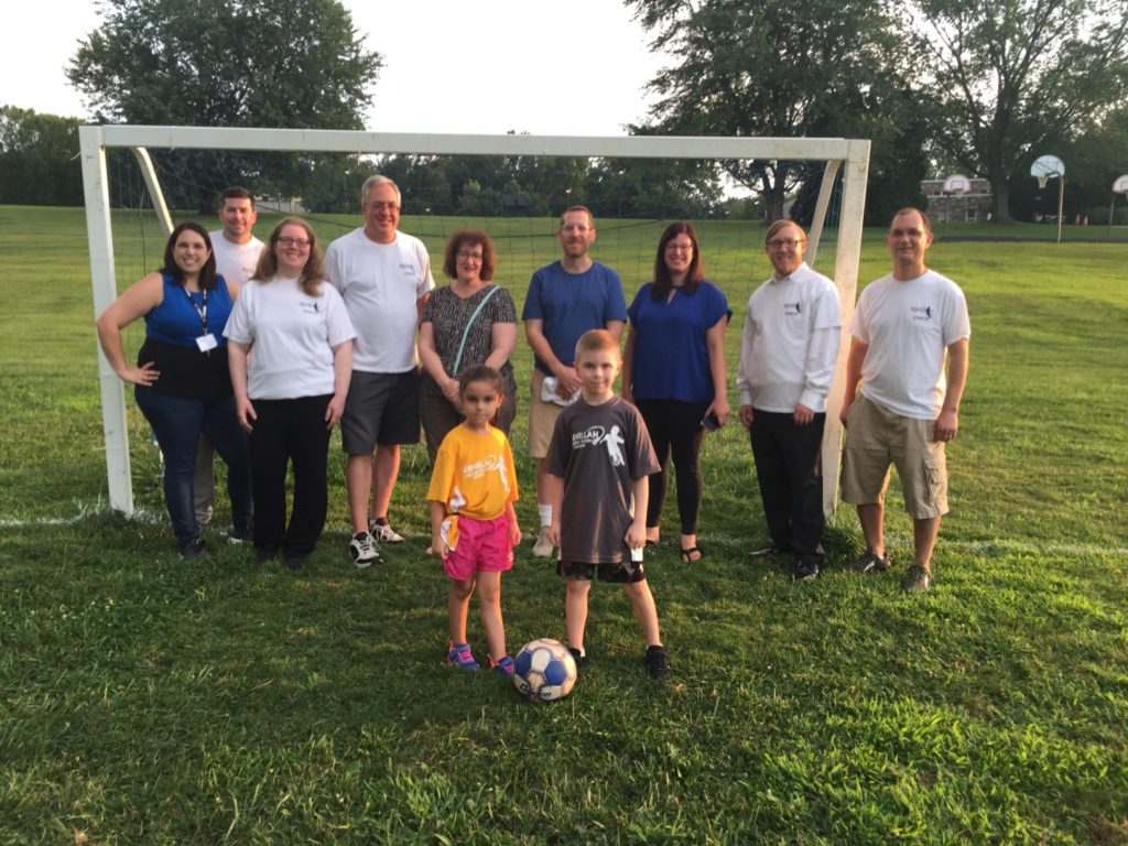 A group of adults and two kids with a soccer ball on a soccer field