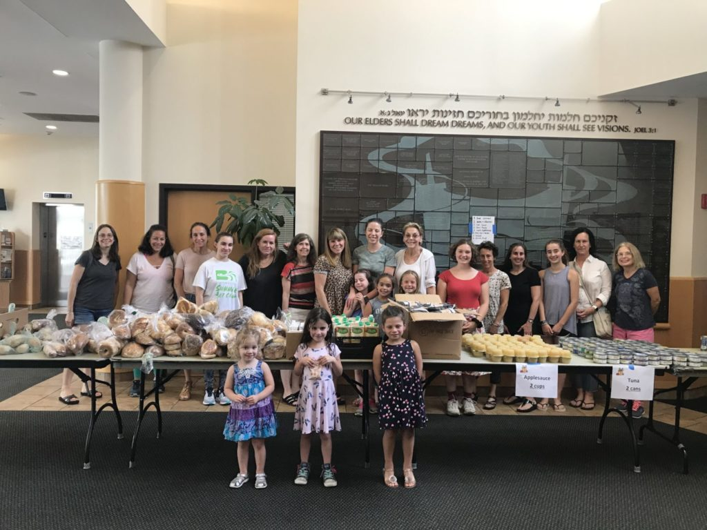Congregants of all ages at Main Line Reform Temple surrounded by food products