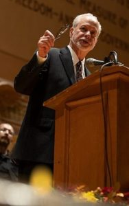 Rabbi Hazzan Jeffrey Myers speaks at a podium for a Tree of Life vigil
