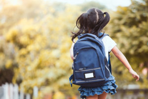 a girl with black hair in pigtails and a blue backpack runs