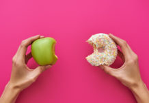 a person holds an apple and a donut