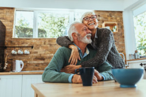 an older couple hugging at a kitchen table