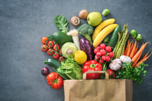 a paper grocery bag bursting with vegetables
