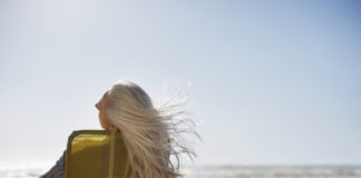 woman sitting in a chair on the beach with her hair blowing in the wind