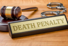 a desk name plate that says death penalty next to a gavel and handcuffs