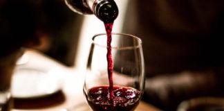 a bottle of kosher Manischewitz wine being poured into a wine glass