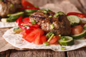 lamb burgers with diced tomato  and cucumber on pita