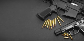 two firearms surrounded by bullets