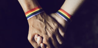 two people holding hands with lgbtq rainbow armbands