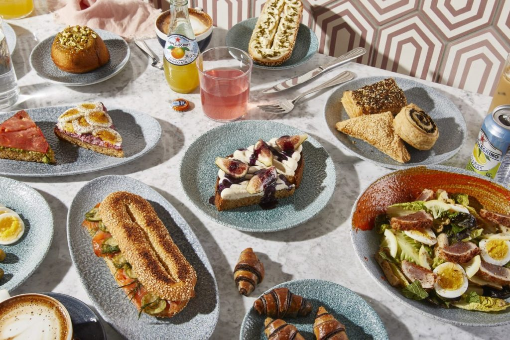 Different dishes at K'Far including rugelach, Jerusalem bagel with lox, kubaneh toast with dates and more