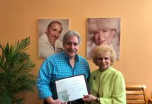 John Birnhak accepts a Negev Society scroll from Claire Winick