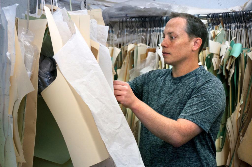 Scott Savett goes through hangers of clothing