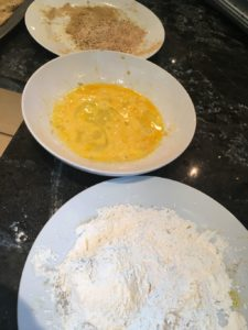 A bowl of bread crumbs, a bowl of beaten eggs and a bowl of flour
