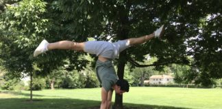 Brian Ungar does a handstand with his legs spread on a picnic table