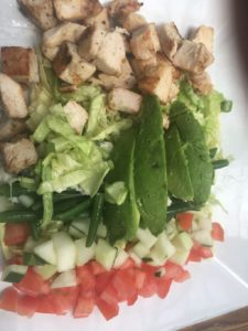 a salad of lettuce, tomato, cucumber and grilled chicken