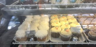 coconut cream, carrot cake and chocolate and vanilla cupcakes in a display case at Cake
