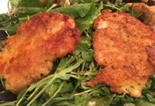 two pieces of breaded chicken on a bed of greens