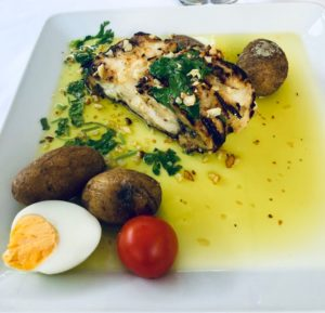 a dish of cod with cilantro, potatoes, half a hard boiled egg and olve oil