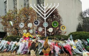 flowers next to a large menorah outside Tree of Life synagogue