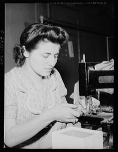 a black and white photo of a garment worker