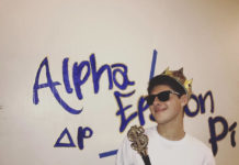 Jake Riesenbach wearing a crown, holding a staff with a dollar sign, with alpha epsilon pi on the wall behind him