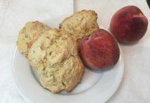 Three scones next to two peaches
