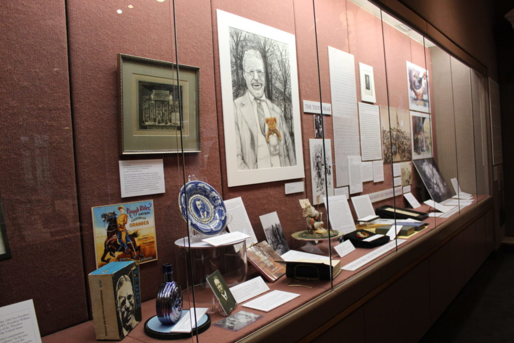 A display case of drawings and other artifacts