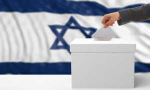 A voter places a card in a box with an israeli flag in the background