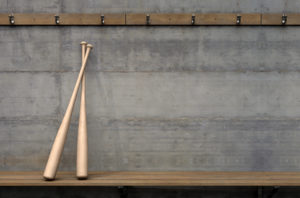 two baseball bats leaning against the wall