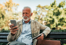a white-haired man sits on a park bench looking at his phone