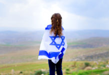 girl looks over a valley with an Israeli flag wrapped around her